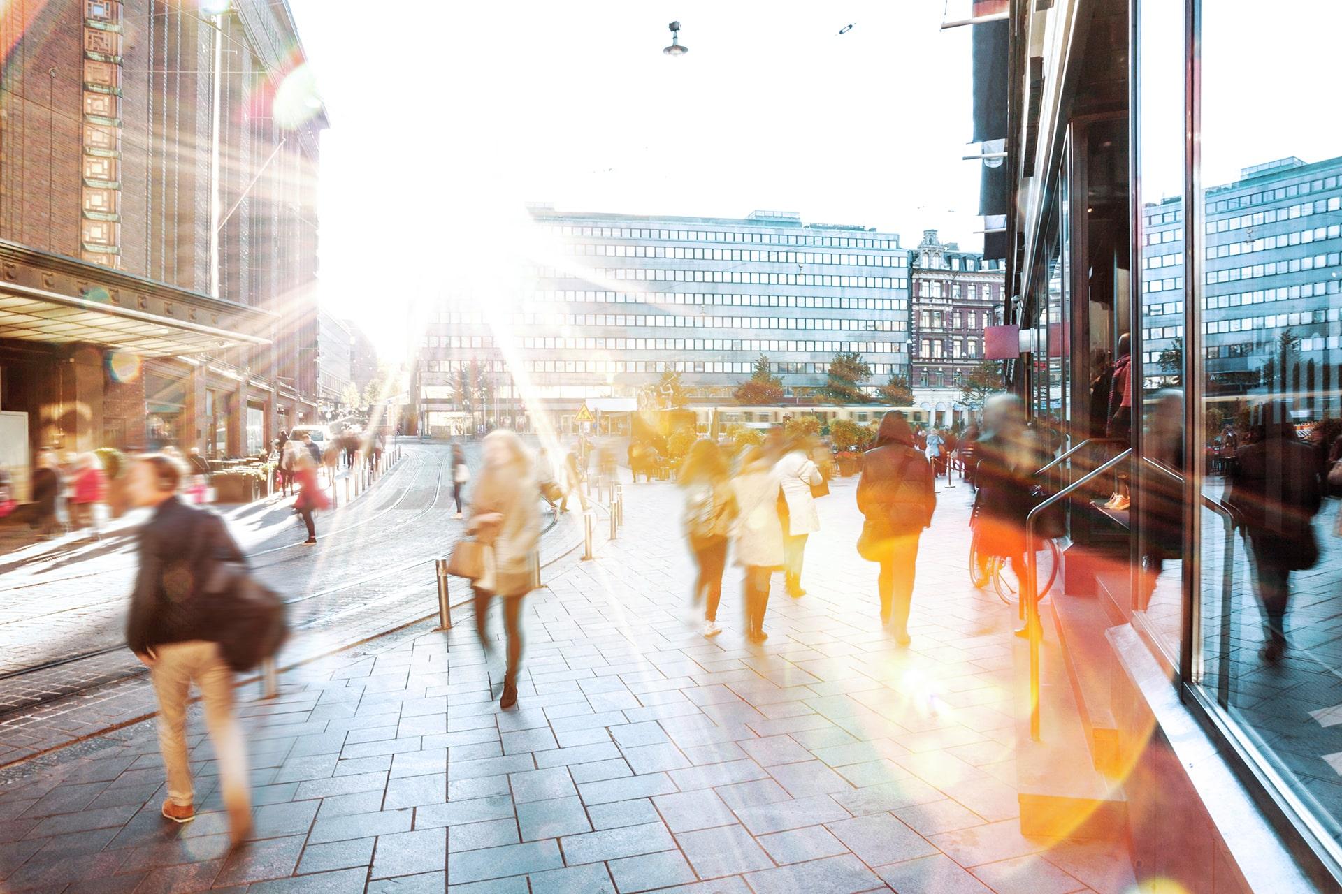 Ihmiset kulkemasas Helsingissä, aurinko heijastaa linssiin.